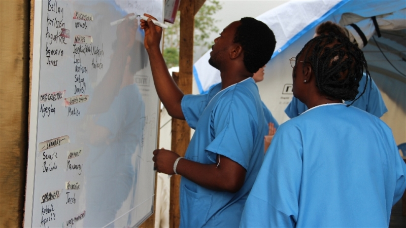 Health workers outline the day's activities at the IFRC Ebola treatment centre outside of Kenema, Sierra Leone. (Oct 2014)  © Anna Jefferys/IRIN