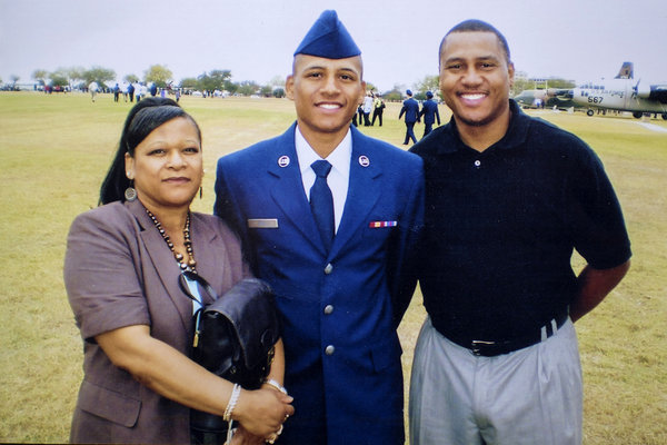Mr. Hill, center, with his parents, Carolyn Giummo and Anthony Hill.
